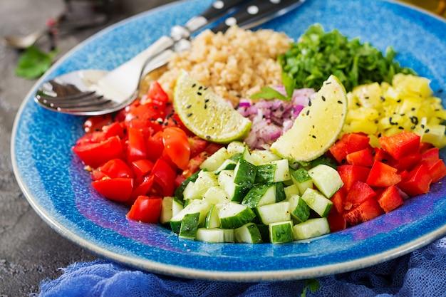 Ensalada con quinua, rúcula, pimientos, tomates y pepino en un recipiente sobre un fondo oscuro. comida sana, dieta, desintoxicación y concepto vegetariano. tazón de buda.
