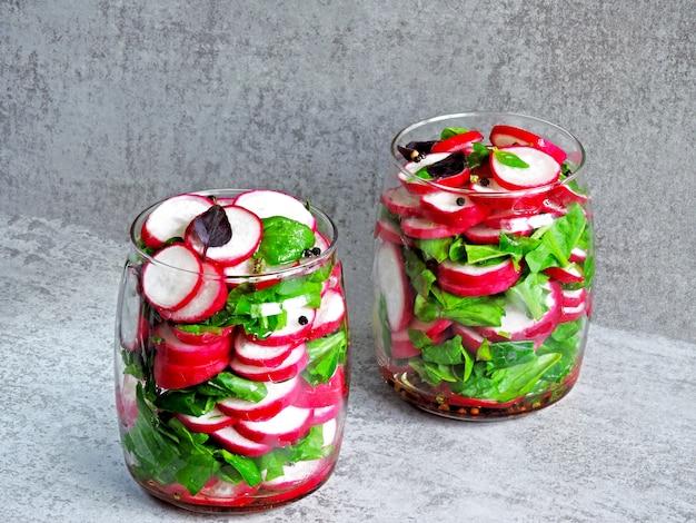 Ensalada de rábano con espinacas en un frasco. ensalada de fitness en el frasco. ensalada de verduras en un frasco para llevar.