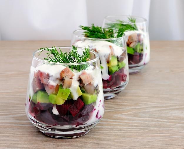 Ensalada de remolacha con aguacate y arenque en salsa de crema en un vaso