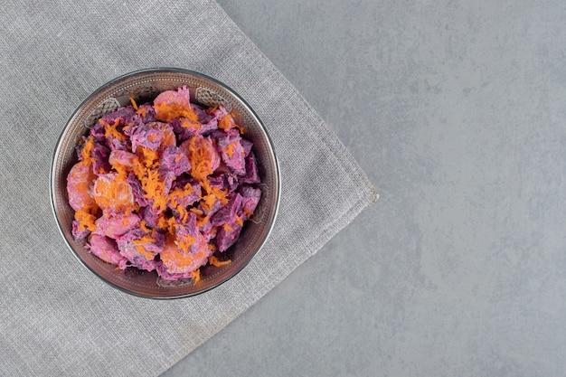 Ensalada de remolacha morada con rodajas de zanahoria y crema agria en un recipiente metálico