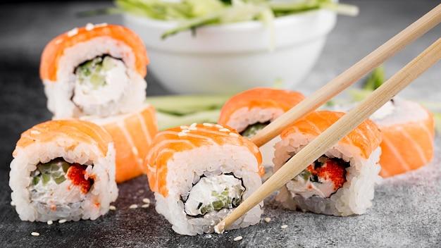 Ensalada y rollos de sushi frescos y palillos