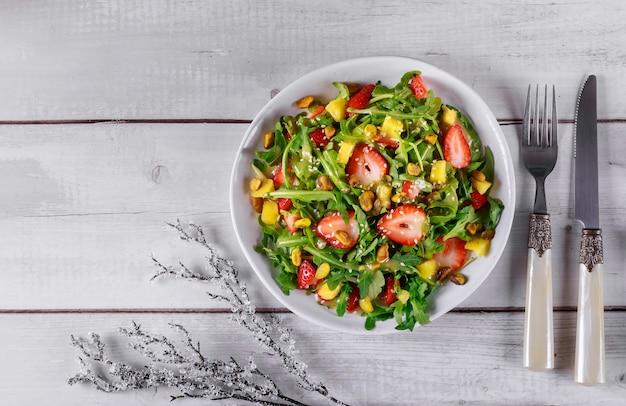 Ensalada de rúcula con fresas, piña y pistachos, semillas de sésamo, aceite y limón contenido navideño