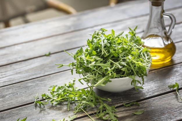 Ensalada de rúcula fresca con aceite de oliva en un plato blanco sobre la mesa de madera.