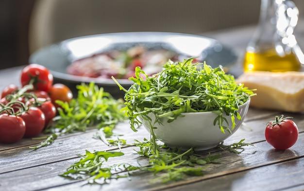 Ensalada de rúcula fresca en un plato blanco sobre la mesa de madera.