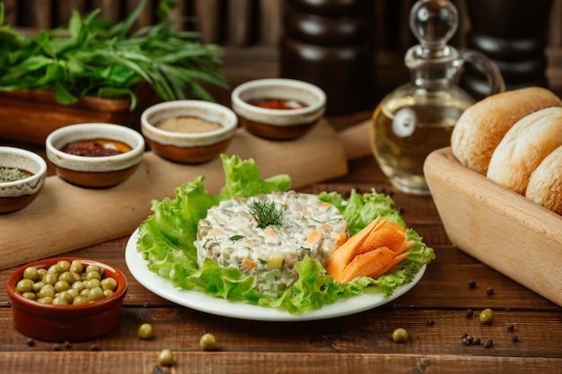Ensalada rusa stolichni servida en hojas de ensalada verde y zanahoria decorativa con judías verdes