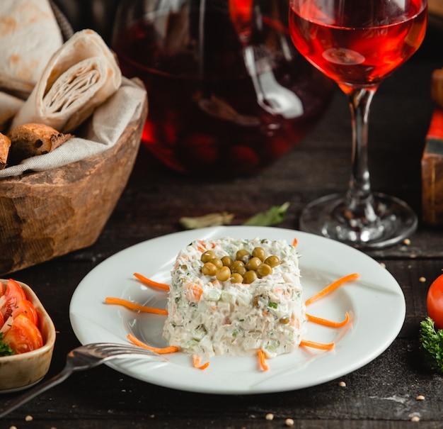 Ensalada rusa stolichni con vino tinto y pan.