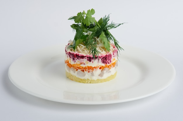 Ensalada rusa tradicional de arenque con remolacha, zanahoria, papa, huevos, queso y mayonesa