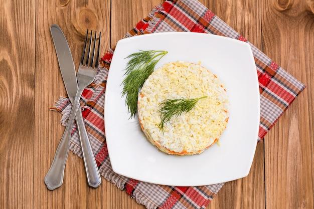 Ensalada rusa tradicional con verduras y pescado mimosa