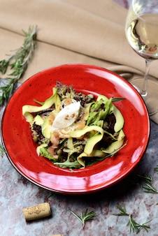 Ensalada de salmón, aguacate y alcaparras en un plato rojo.
