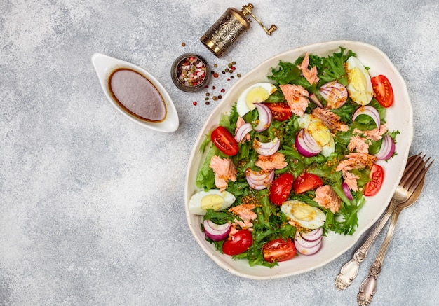 Ensalada de salmón delicatessen fresco con lechuga, tomate, huevo y cebolla morada