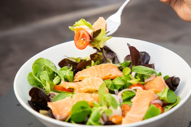 Ensalada de salmón fresco con tomates dulces, ajo en vinagre, cebolla y espinacas son una dieta saludable para cada comida.
