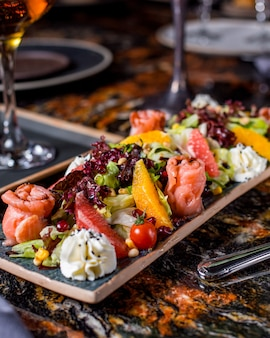 Ensalada de salmón con lechuga, tomate, maíz, naranja, pomelo, granada y nata