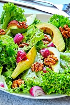 Ensalada saludable con aguacate, cebolla azul y nueces. ensalada keto superalimentos