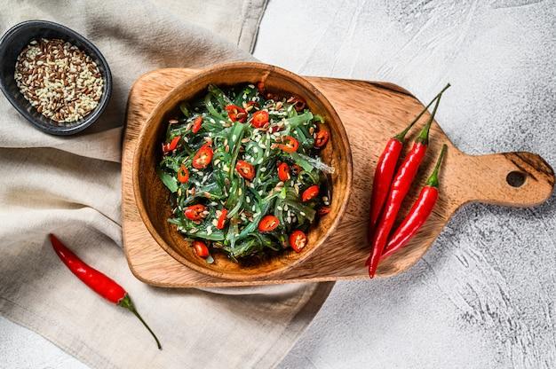 Ensalada saludable de algas chuka con verduras y ají rojo. vista superior