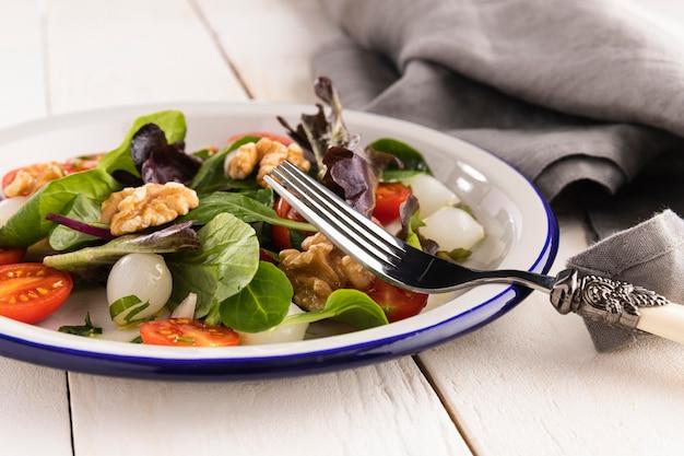Ensalada saludable en arreglo de plato blanco