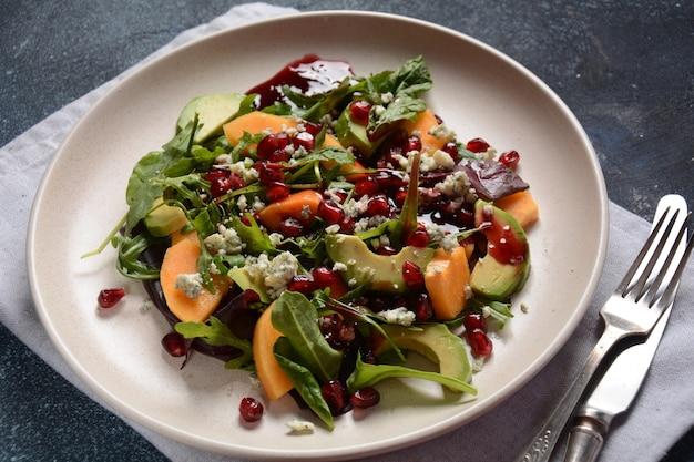 Ensalada saludable de caqui, queso azul, espinacas, rúcula, hojas de lechuga en la placa blanca.