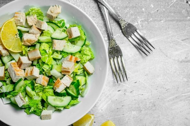 Ensalada saludable. ensalada de pepinos, pollo y col china vertida en jugo de limón. sobre un rústico.