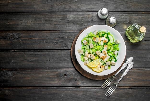 Ensalada saludable. ensalada de pepinos, pollo y col china vierte jugo de limón sobre mesa de madera.