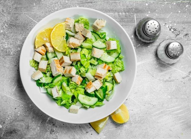 Ensalada saludable. ensalada de pepinos, pollo y repollo chino vierte jugo de limón sobre mesa rústica.