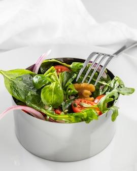 Ensalada saludable en forma redonda de metal con un tenedor