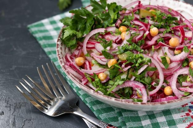 Ensalada saludable con garbanzos, papas, cebollas rojas y pepinos en vinagre en un plato