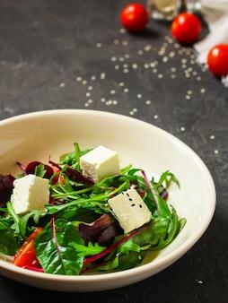 Ensalada saludable de hojas en un plato blanco y queso (mezcle los greens, jugoso snack). fondo de comida