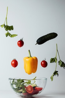 Ensalada saludable con ingredientes vegetales voladores en blanco