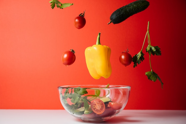 Ensalada saludable con ingredientes vegetales voladores en rojo