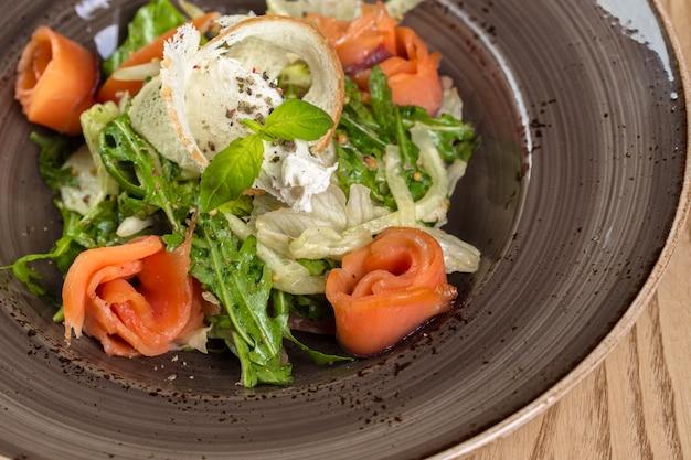 Ensalada saludable de pescado rojo con hojas de lechuga mixtas