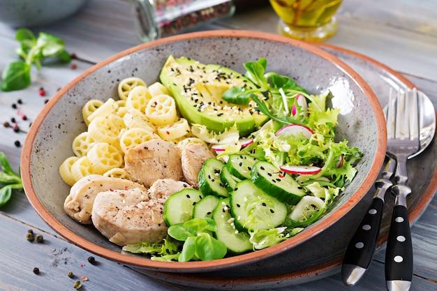 Ensalada saludable con pollo, aguacate, pepino, lechuga, rábano y pasta en la mesa oscura. nutrición apropiada. menú dietético cena.