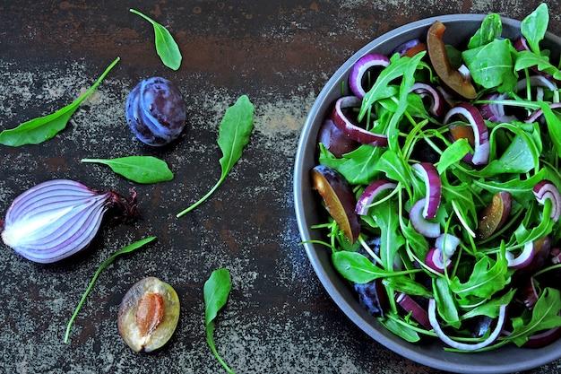 Ensalada saludable con rúcula, ciruela y cebolla azul en un recipiente sobre un elegante fondo cutre