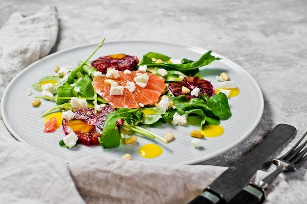 Ensalada saludable con rúcula, toronja, naranjas rojas, nueces y queso de tofu.