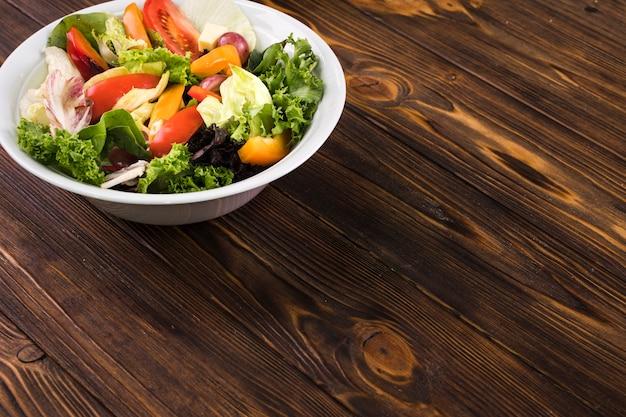 Ensalada saludable sobre fondo de madera
