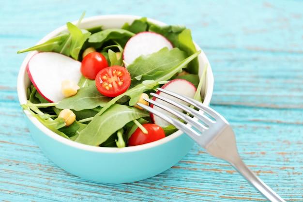 Ensalada saludable en un tazón en la mesa de madera azul