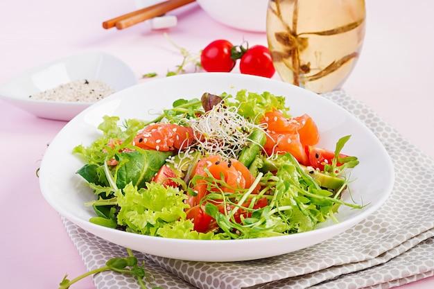 Ensalada saludable con vegetales frescos, tomates, aguacate, rúcula, semillas y salmón.