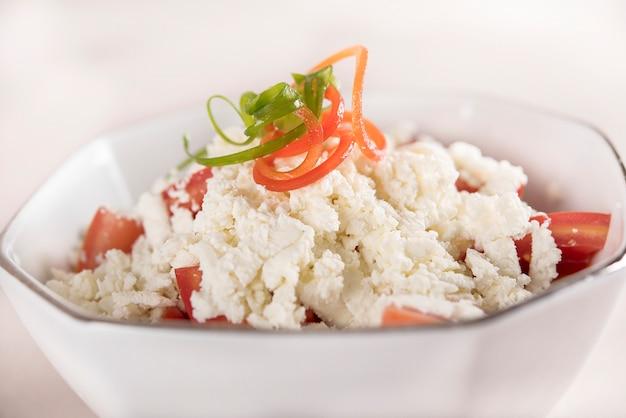 Ensalada sencilla de tomate y queso, decorada con hojas verdes y rojas.