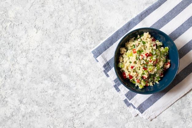 Ensalada tabulé con cuscús, perejil, limón, tomate, aceite de oliva. ensalada vegetariana levantina. cocina libanesa, árabe. fondo claro. vista superior. espacio para texto