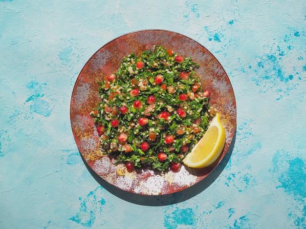 Ensalada tabulé con cuscús en un tazón rojo sobre mesa rústica azul