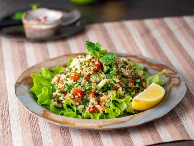 Ensalada de tabulé con quinua. comida oriental con mezcla de verduras, dieta vegana.