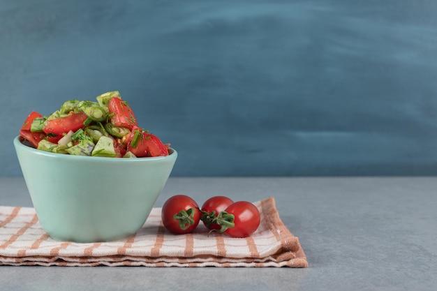 Ensalada en taza azul con una mezcla de frutas y verduras picadas.