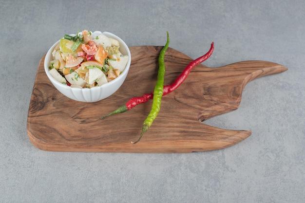 Ensalada de temporada de ingredientes mixtos con verduras y frutas en un plato blanco.
