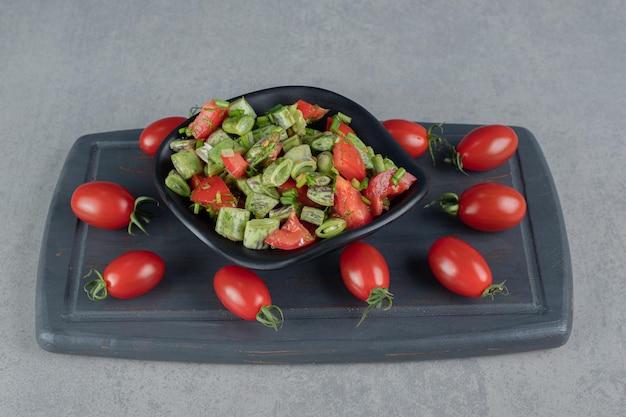 Ensalada de temporada con tomates cherry rojos y judías verdes.