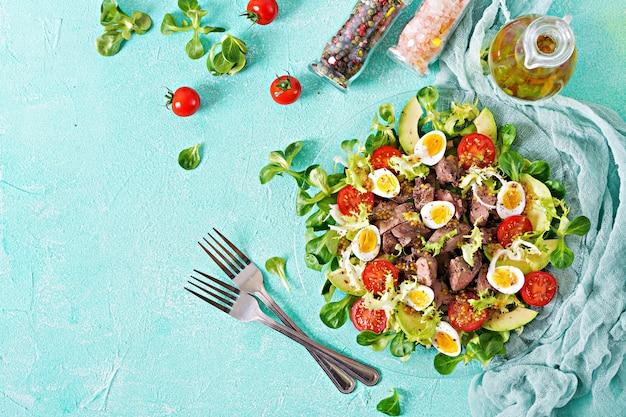 Ensalada tibia de hígado de pollo, aguacate, tomate y huevos de codorniz. cena saludable. menú dietético endecha plana. vista superior