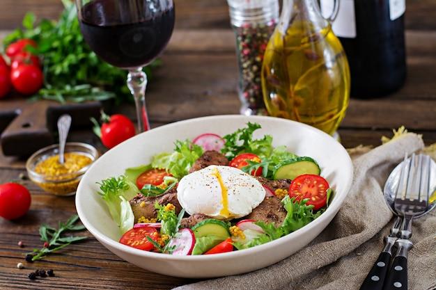 Ensalada tibia de hígado de pollo, rábano, pepino, tomate y huevo escalfado. comida sana.