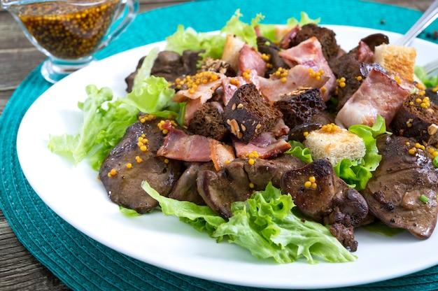 Ensalada tibia y saludable de hígado de pollo, crutones de centeno, tocino ahumado, ensalada verde y salsa de mostaza en un plato blanco o. de cerca