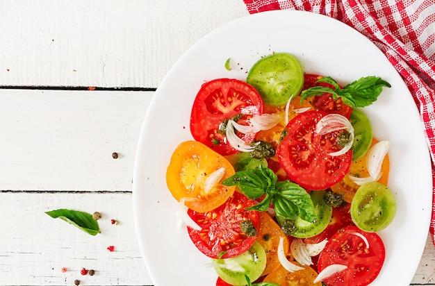 Ensalada de tomate coloreado con cebolla y pesto de albahaca.