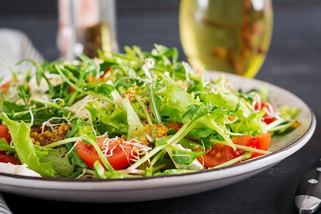 Ensalada de tomate con mezcla de micro verdes y queso camembert.