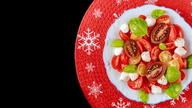 Ensalada de tomate con mozzarella y albahaca para la cena de navidad. plato vegetariano.