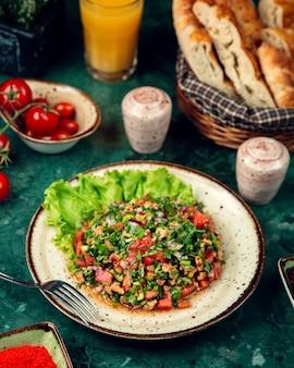 Ensalada de tomate con nuez, pimiento, cebolla y hierbas