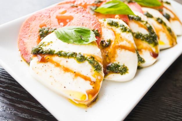 Ensalada de tomate y queso mozzarella en plato blanco
